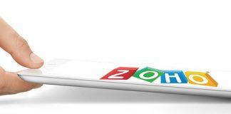 Mano dejando una tablet con el logo de zoho sobre fondo blanco