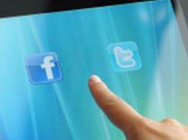 Manos sujetando una tablet con los logos de facebook y twitter