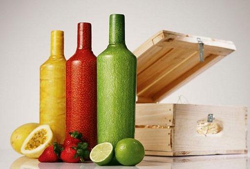 botellas roja verde y amarilla en una mesa con una caja detras y frutas