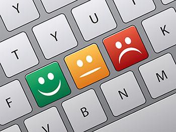 teclas con cara sonriente neutra y triste en el teclado de un dispositivo tactil