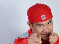 hombre con gorra y chandal rojo en una habitacion con la pared blanca haciendo un saludo