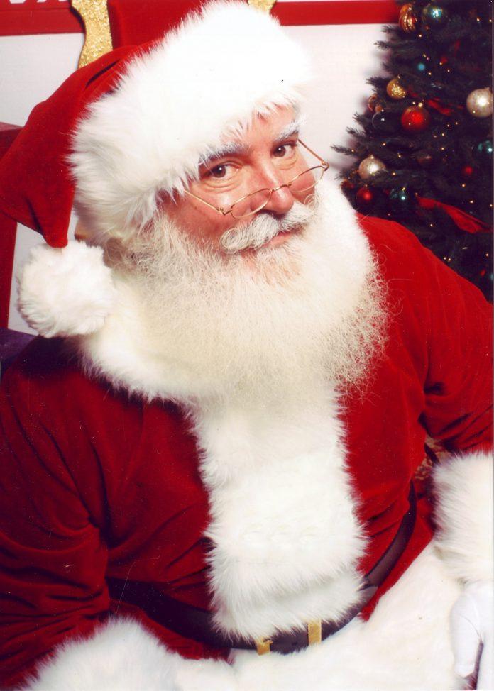 hombre vestido de papa noel sentado al lado de un arbol de navidad