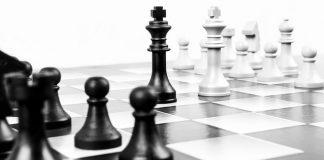 figuras del rey de ajedrez blanca y negra enfrentadas en un tablero de ajedrez
