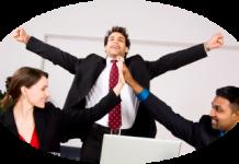 hombre trajeado en una oficina blanca sonriendo y estirandose feliz con sus compañeros de trabajo
