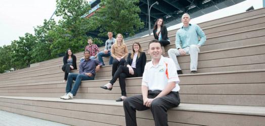 grupo de personas sonrientes en el exterior de un establecimiento sentados
