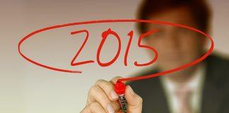hombre con traje en una oficina de cara escribe 2015 con rotulador rojo