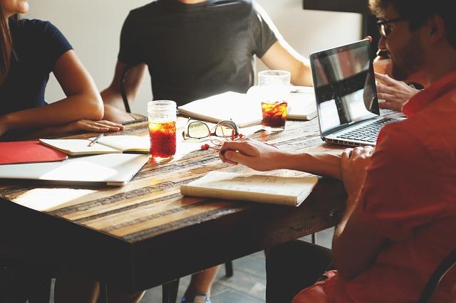 equipo de trabajo en una oficina sentados al rededor de una mesa reunidos