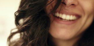sonrisa de chica joven atractiva con pelo largo castaño ondulado