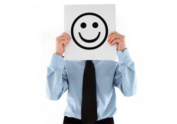 hombre con camisa azul y corbata tapando su rostro sujetando una cara feliz