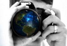 hombre con una camara de fotos y objetivo don el planeta tierra
