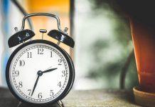 despertador analogico negro en una mesa de una habitacion marcando la hora