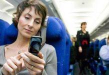 mujer con el pelo corto en el asiento azul de un avion usando el movil