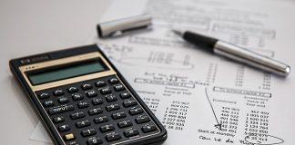 calculadora negra y boligrafo sobre una mesa con documentos de contabilidad