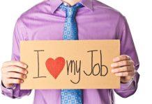 """hombre con camisa morada y corbata sujetando un papel con mensaje de """"i love my job"""""""