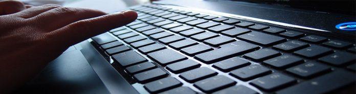 mano de una persona tecleando en un ordenador portatil