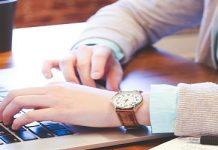 persona con un reloj en una mesa de madera de una oficina trabajando con el ordenador