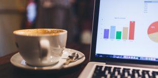 taza de cafe encima de una mesa al lado de un ordenador portatil con gráficos pantalla