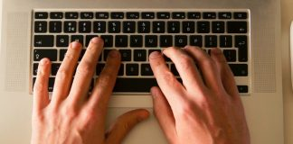 manos sobre teclado de un ordenador portatil en una mesa blanca de una oficina tecleando