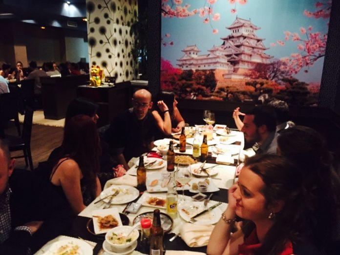 grupo de personas en un restaurante chino hablando mientras cenan