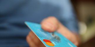 mano sujetando una tarjeta de credito azul