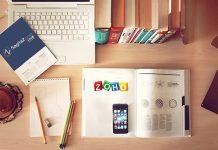 libro con el logo de zoho y sagitaz en escritorio de madera y un ordenador portatil