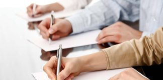 manos escribiendo en un folio sobre un escritorio de madera