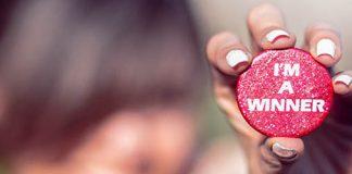 """chica con flequillo en la calle enseñando un pin rojo con la frase """"i'm a winner"""""""