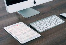 apple mac y una tablet en pantalla un calendario sobre una mesa de madera de una oficina