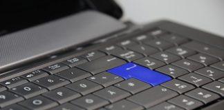 tecla de enter de color azul en un teclado negro de un ordenador