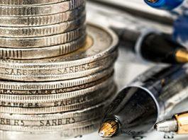 torre de monedas sobre documentos y boligrafos