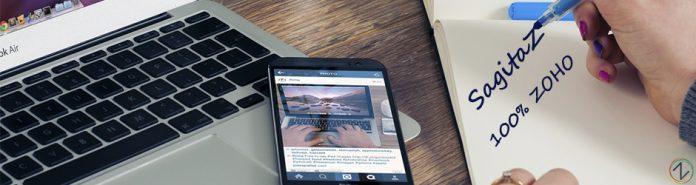 movil con la aplicacion de instagram sobre ordenador portatil y una mujer escribe en cuaderno sagitaz