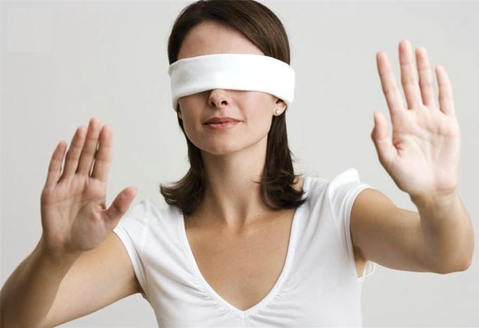 mujer morena en una habitación con venda en los ojos