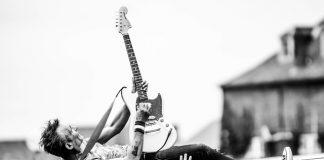 hombre rockero en un concierto tocando la guitarra electrica encima del publico