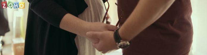 logo de zoho hombre y mujer en una habitación blanca cogiendose de las manos
