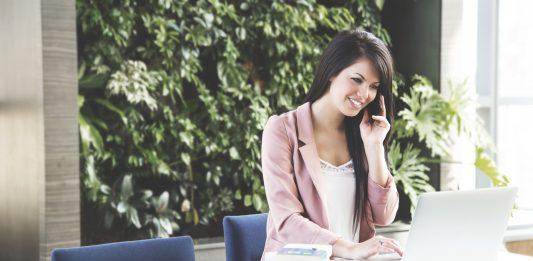 chica joven con americana rosa en una oficina sentada frente al ordenador trabajando