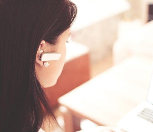 chica con aparato de manos libres en una oficina luminosa trabajando con el ordenador