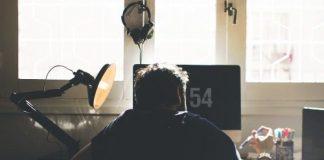 hombre con camiseta en un estudio sentado de espaldas frente al ordenador trabajando