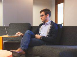 hombre con gafas en una oficina sentado en un sofa trabajando con zoho