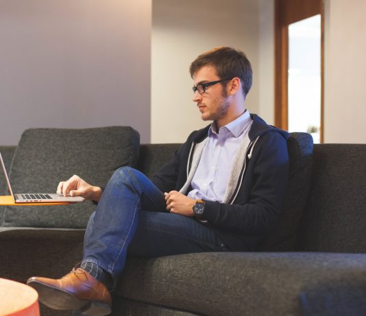 hombre con gafas en una oficina sentado en un sofa trabajando con el ordenador portatil