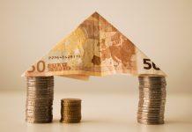 monedas de euro apiladas y un billete de euro formando una casa sobre una mesa blanca