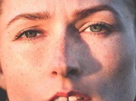 mujer con los ojos verdes y pecas de primer plano mirando al frente