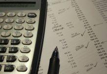 calculadora cientifica y boligrafo negro sobre una hoja con cifras llevando las cuentas