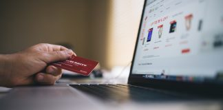 mano de una persona sujetando una tarjeta de credito para pagar una compra online