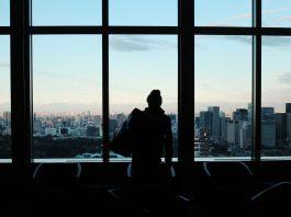 hombre con gorro y mochila en oficina de espaldas mirando por la ventana