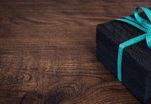 regalo envuelto negro con lazo celeste en mesa de madera