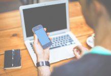 Persona mirando móvil junto a ordenador tomando cafe en una mesa de madera