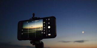 movil en un tripode fotografiando el mar en el atardecer