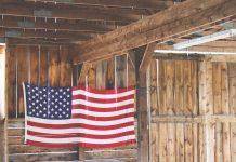 Bandera de Estados Unidos de tela grande colgada en una pared de madera