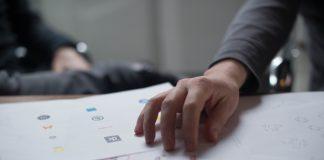 Mano de un hombre sobre un documento encima de una mesa de oficina trabajando