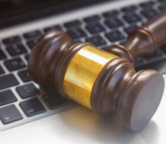 Mazo de juez sobre un ordenador portail gris